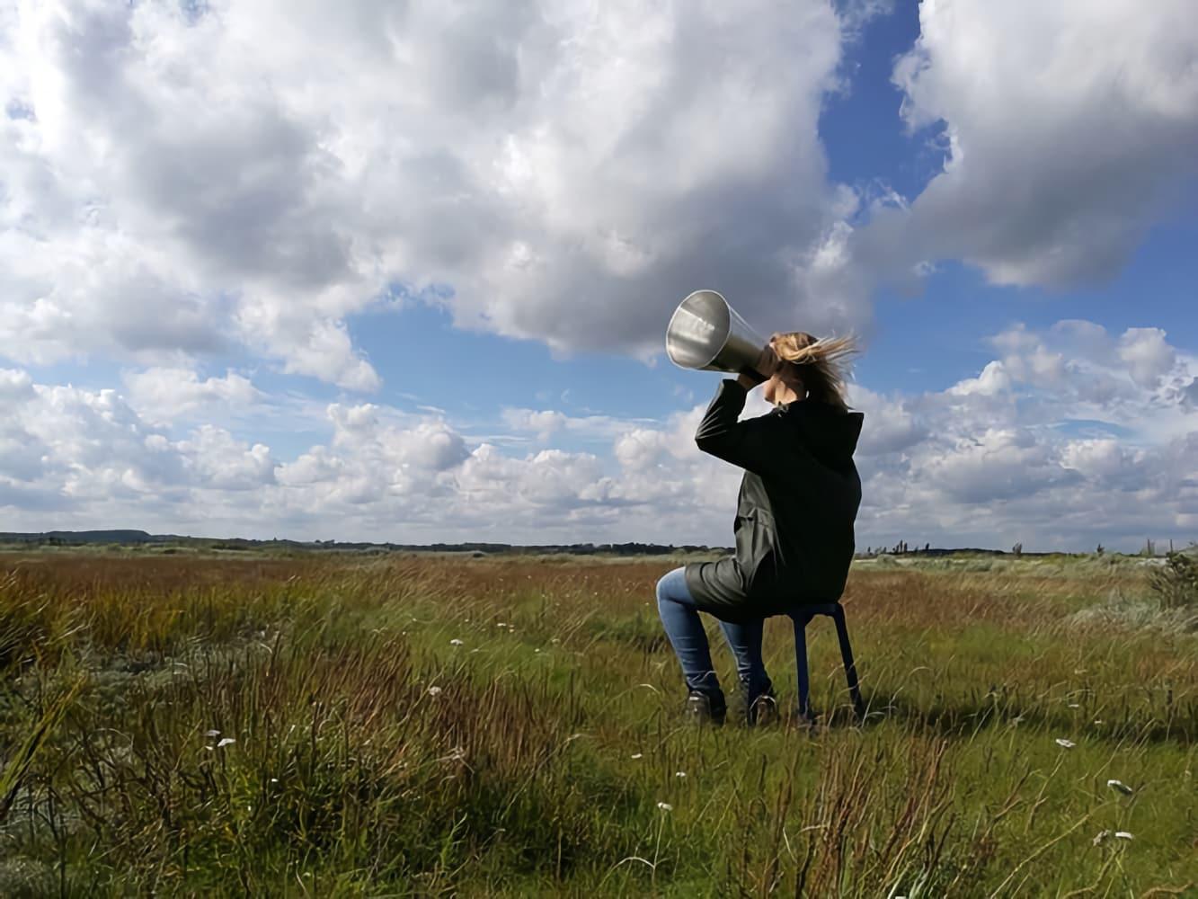 Sandra Boss listening in a field